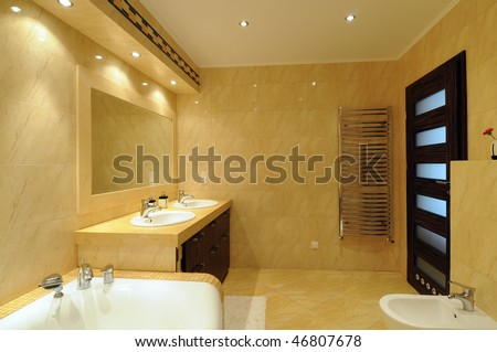 Interior of a modern bathroom with a mirror, lights and tub.