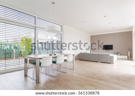 Interior of a modern bright dining-room with large windows #361338878