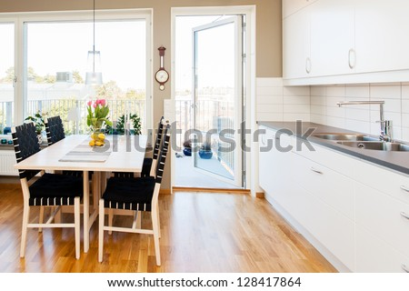 interior of a modern kitchen with dining-table by the window and white cupboards