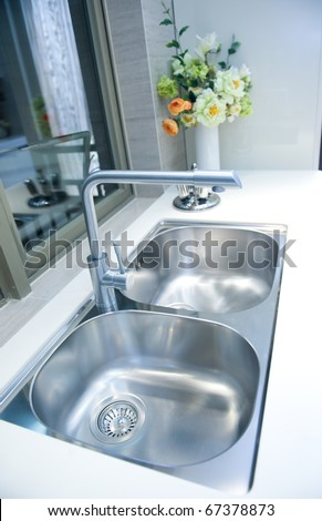 Interior of a modern kitchen with stanless steel double sink.