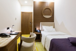 Interior of a modern new hotel single bed bedroom in the evening