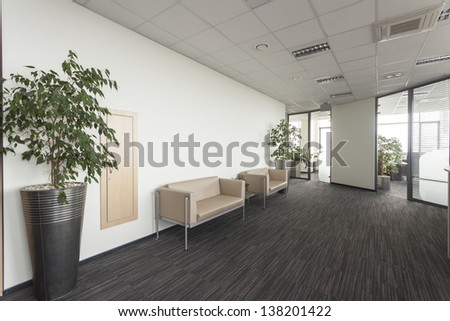 Interior of a modern office corridor with two sofa