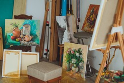 Interior of a painters studio or gallery with colorful canvases covering a variety of subjects hanging on the wall and an unfinished painting on a wooden easel. Studio of painting