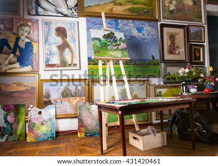 Interior of a painters studio or gallery with colorful canvases covering a variety of subjects hanging on the wall and an unfinished painting on a wooden easel #431420461