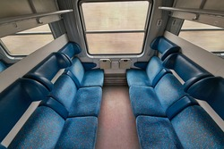 Interior of a passenger train wagon with cabin compartments, empty seats