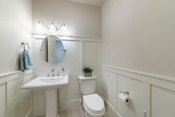 Interior of a powder room with half wooden panel and lights. There are full pedestal basin with mirror near the towel hanging on the towel holder and a two piece toilet bowl with potted plants on top.