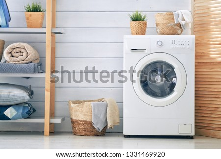 Interior of a real laundry room with a washing machine at home #1334469920