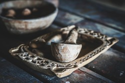 Interior of a Slavic traditional house from early medieval times. Dugout wooden spoon and carved tray. Wooden bowl and walnuts in the background. Table with kitchen utensils. Medieval kitchenware.