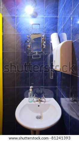 Interior of a small restaurant toilet, simple and blue.