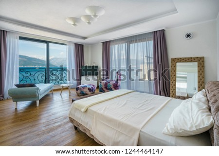 Interior of a spacious light bedroom with sea view in a luxury villa. Big comfortable double bed in elegant modern bedroom #1244464147