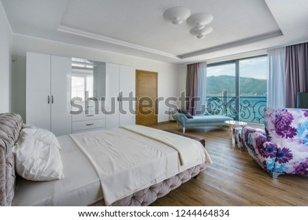 Interior of a spacious light bedroom with sea view in a luxury villa. Big comfortable double bed in elegant modern bedroom #1244464834