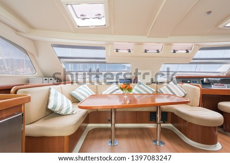 Interior of a stunning modern private sailing catamaran, portraying the saloon with big lounging area with cushions  #1397083247