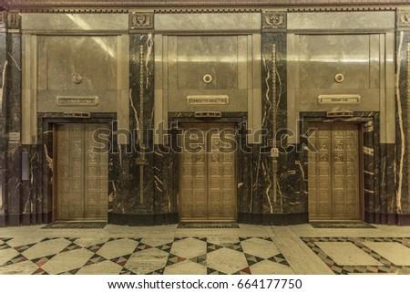 Interior of a vintage skyscraper with golden elevators
