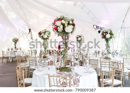 Interior of a wedding tent decoration ready for guests. Served round banquet table outdoor in marquee decorated flowers and silk. Catering concept #790009387