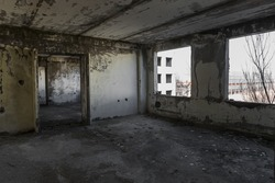 Interior of abandoned administrative building. Interior ruins of industrial factory. An old concrete staircase, ruins, corridor with garbage and mud, ruined walls of  unfinished office business center