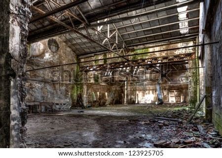 interior of abandoned factory with rubble and debris - desolate room of an old destroyed industrial warehouse - hdr image