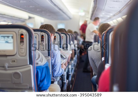Interior of airplane with passengers during flight.