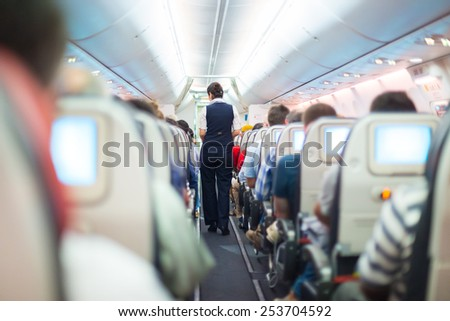 Interior of airplane with passengers on seats and stewardess in uniform walking the aisle.