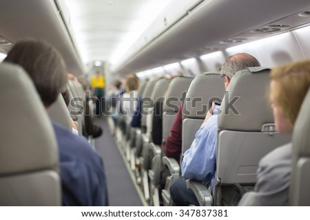 Interior of airplane with passengers on seats waiting to taik off. Stewardess in green uniform providing final safety instructions. Horizontal composition.