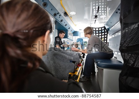 Interior of ambulance with senior woman being transported to hospital, caregiver at side - stock photo