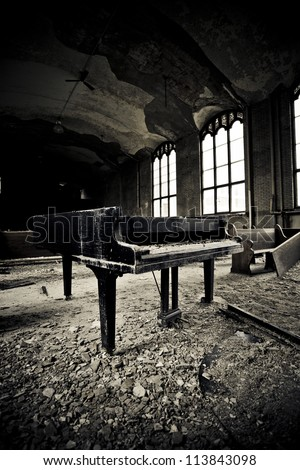Interior of an abandoned school there is a grand piano that has been left to the ravages of time in Detroit Michigan .