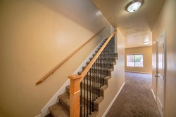 Interior of an empty house with stairs and carpeted flooring. Hallway interior beside the carpeted stairs with wooden handrail and metal baluster, across a closed white door room and windows.