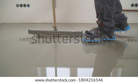 Interior of apartment under construction. Mirror smooth surface of the floor. Floor covering with self leveling cement mortar. Roller application Foto d'archivio ©