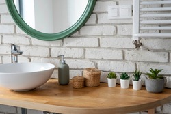 Interior of bathroom with modern design. White bricks,design basin and wooden counter with cactus. Bright indoor in industrial style and modern architecture.