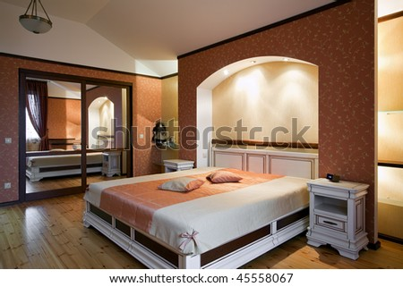Interior of beautiful bedroom with white wooden furniture and red patterned wallpapers