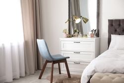 Interior of bedroom with dressing table near wall