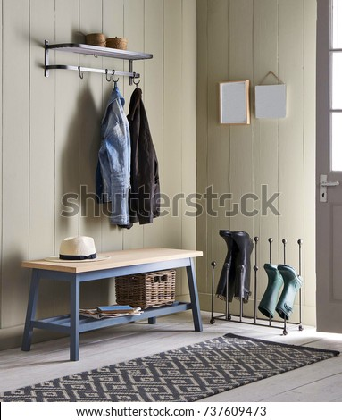 Interior of bright hallway home. Hanging clothes on door #737609473