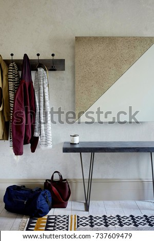 Interior of bright hallway home. Hanging clothes on door #737609479