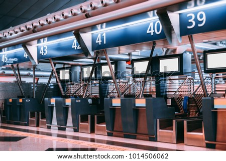 Interior of check-in area in modern airport: luggage accept terminals with baggage handling belt conveyor systems, multiple blank white information LCD screen templates, indexed check-in desks