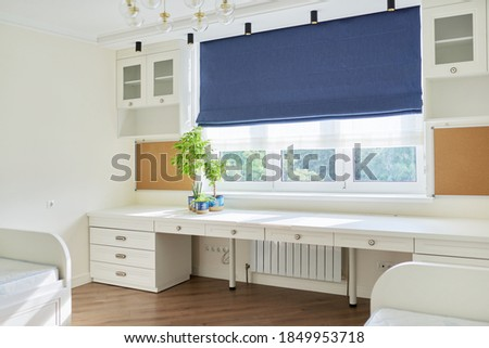 Interior of children's room for two children in light colors. White furniture, table, blue roman blind on the window Foto stock ©