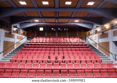 Interior of cinema auditorium with lines of chairs.