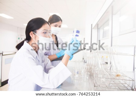 Interior of clean modern white medical or chemistry laboratory background. Laboratory scientists working at a lab with test tubes. Laboratory concept with Asian woman chemists.