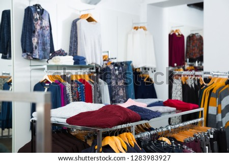 Interior of clothing shop with blouses and cardigans on hangers and shelfs
