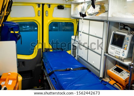 Interior of contemporary ambulance car with stretcher, dropper, first aid kits, refrigerator and medical equipment #1562442673