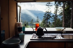 Interior of converted camper van or camping RV kitchen, coffee kettle and grinder stand on indoor table. Concept vanlife on the road, outdoor camp vibes for digital nomads