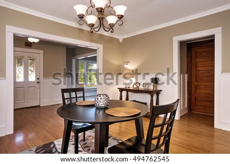Interior of dining room  with black round table and two chairs standing on colorful rug. Wall panels and hardwood floor. Northwest, USA #494762545