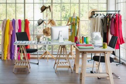interior of dressmaker shop with dressmaking working desk and hanging rack with dress