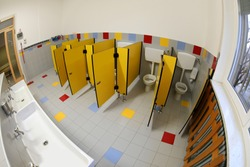Interior of Empty bathroom of a daycare center with small yellow doors and white ceramic sink photographed by fisheye lens without children