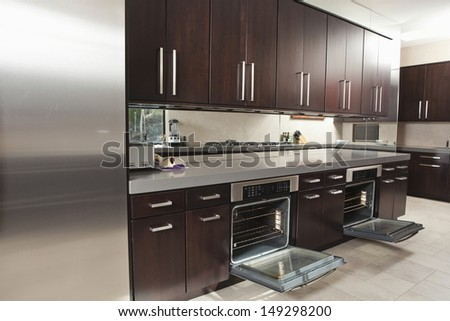 Interior of empty commercial kitchen with open oven and cabinets ...