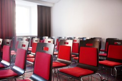 Interior of empty modern meetingroom. Conference room in a hotel for business training. Rows of chairs and desks. Boardroom with presentation screen and projector.