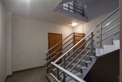 Interior of entrance in modern residential complex. Staircase. Block of flats. Wooden doors.