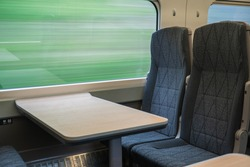 Interior of fast moving train showing seats and table with blurred out countryside background seen through the window