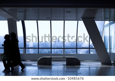 interior of futuristic building with bench, people move