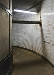 Interior of Greenwich foot tunnel, dirty grunge walls and floor in narrow corridor lit by neon light