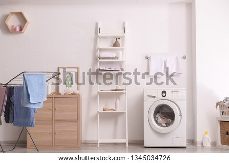 Interior of home laundry room with modern washing machine #1345034726