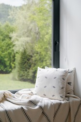 Interior of home room with window, house design. Nobody at sill, modern decor for cozy indoor place. Scandinavian comfortable apartment. Vertical closeup of pillow, blanket at windowsill.